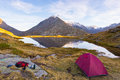 Camping with tent near high altitude lake on the Alps. Reflection of snowcapped mountain range and scenic colorful sky at sunset. Royalty Free Stock Photo