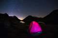 Camping under starry sky and Milky Way arc at high altitude on the italian french Alps. Glowing tent in the foreground. Adventure