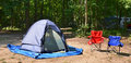 Campsite with chairs and tent among trees Royalty Free Stock Photography