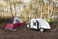 Campsite with teardrop trailer and tent in the forest Stock Photo