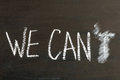 We can t replaced by we can message isolated on black background letter erased chalk drawing on blackboard business concept Royalty Free Stock Photo