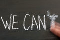 We can t replaced by we can message isolated on black background letter erased a moving hand chalk drawing on blackboard Royalty Free Stock Image