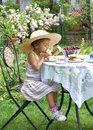 Can t wait for cake small pretty little girl eagerly eating with sandwiches on her plate playing dressup Royalty Free Stock Photos