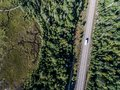 Beautiful Canada camper bus driving on road endless pine tree forest with lakes moor land aerial view travel background Royalty Free Stock Photo