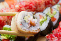 Canada sushi roll sliced in chopsticks on made dish background Stock Image
