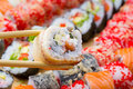 Canada sushi roll sliced in chopsticks on made dish background Royalty Free Stock Photos