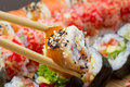 Canada sushi roll sliced in chopsticks on made dish background Royalty Free Stock Images