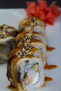 Canada sushi roll sliced in chopsticks on made dish background Stock Images
