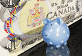 Canadian dollar piggy bank a one bill and blue and white dotted on reflective black surface Stock Photo