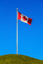 Canadian flag and pole against blue sky Stock Image