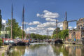 Canal in gouda holland windmill and historical boats a Royalty Free Stock Images