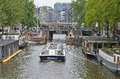 Canalboat in amsterdam a about to pass under a small bridge Royalty Free Stock Photography