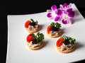 Canape made from biscuit tuna pate tomato pasley and caviar Royalty Free Stock Photography