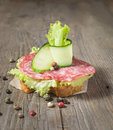 Canape with salami cucumber and salad on wooden table sandwich sausage background Stock Photo