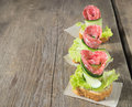 Canape with salami cucumber and salad on wooden table sandwich sausage background Stock Image