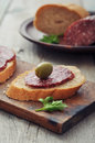 Canape with salami and olives on wooden cutting board closeup Royalty Free Stock Images