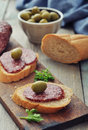 Canape with salami and olives on wooden cutting board closeup Stock Photo