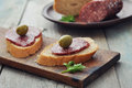 Canape with salami and olives on wooden cutting board closeup Stock Images