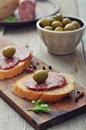 Canape with salami and olives on wooden cutting board closeup Royalty Free Stock Photo