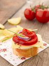 Canape with tomatoes and mozzarella cheese potato chips on wooden table shallow focus vibrant color Royalty Free Stock Image