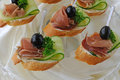 Canapes with ham mini sandwiches and cucumber on a baguette Stock Images