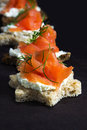 Canapes in star shape with smoked salmon on dark brown wood, fo Royalty Free Stock Photo