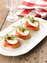 Canapes with tomatoes and mozzarella bruschetta capers on wooden table shallow focus Royalty Free Stock Photos