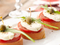 Canapes with tomatoes and mozzarella bruschetta capers on wooden table shallow focus Stock Image