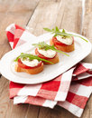 Canapes with tomatoes and mozzarella bruschetta capers on wooden table shallow focus Stock Images