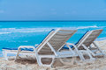 Cancun beach mexico the turquoise waters of the pacific ocean in yucatan peninsula and two chairs on the sand Royalty Free Stock Images