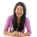 Candid asian woman laughing portrait with mouth opened big sitting isolated on white background Royalty Free Stock Images
