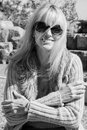 Candid black white portrait mature woman with film grain effec casual of blond wearing sunglasses effect applied Royalty Free Stock Images