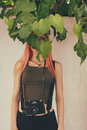 Candid hide retro filtered photograph of a hipster girl hiding her face behind the leaves Royalty Free Stock Photos