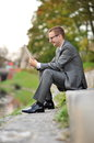 Candid image of young businessman sits using tablet computer near the river Stock Photo