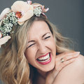 Candid portrait of a laughing bride gorgeous vivacious with long blond hair wearing headband pink orchids close up head shot Stock Photos