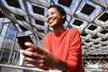 Candid portrait of smiling african american woman holding phone
