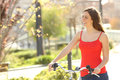 Candid woman walking in an urban park summer or spring carrying a bicycle Stock Image