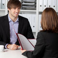 Candidate looking at businesswoman taking interview young male office desk Royalty Free Stock Images