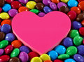 Candies a closeup of colorful sugar coated chocolate with a heart shape in the middle Royalty Free Stock Photo