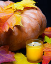 Candle burns and pumpkin with red maple leaf Royalty Free Stock Photo