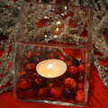 Candle centerpiece cranberries a glass cube with and a lit with it s reflection shining in the glass with beaded garland Royalty Free Stock Image