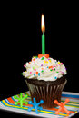 Candle in chocolate cupcake birthday with colorful toy jacks Royalty Free Stock Image