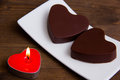 Candle and chocolates in a heart shape on wood close Royalty Free Stock Photo