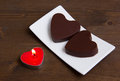 Candle and chocolates in a heart shape on wood Royalty Free Stock Photo