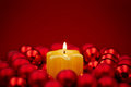 Candle in a christmas wreath burning on red background Royalty Free Stock Photography