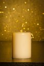 Candle with flame on wood table and gold bokeh background and space for text Stock Photography
