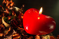 Candle in the form of heart and dry flowers close up Royalty Free Stock Images