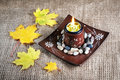 Candle holder and yellow leaves Stock Photography