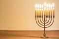 Candle menorah brass with lit candles on a wood table Royalty Free Stock Images