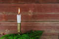 Candle at old barn wall and green decoration Royalty Free Stock Photo